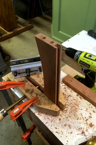I cut a slot along the inner edge of the rails. Using a jig, holes are drilled for dowels.