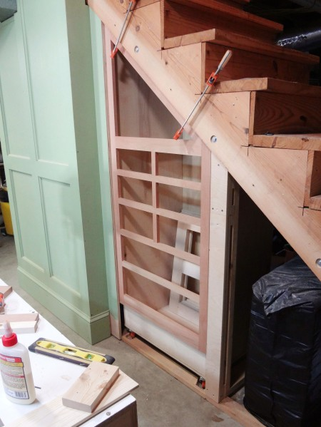 The tool cabinet positioned under the stairs and the face frame clamped in place.