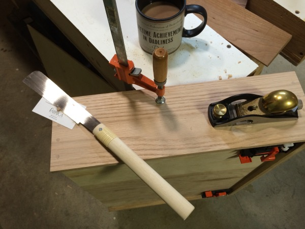 Trimming the dowels via a pull saw and a block plane.