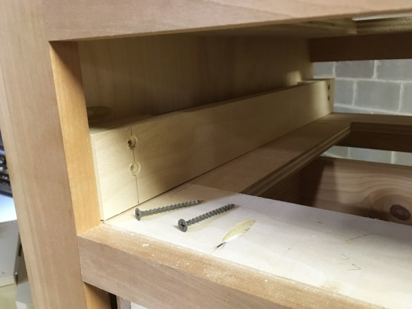 These drawer runners are held in place with screws; no glue.